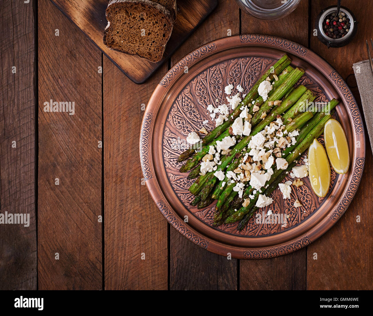 Warm salad of roasted asparagus, feta cheese, nuts, flavored with lemon juice. Top view - Stock Image