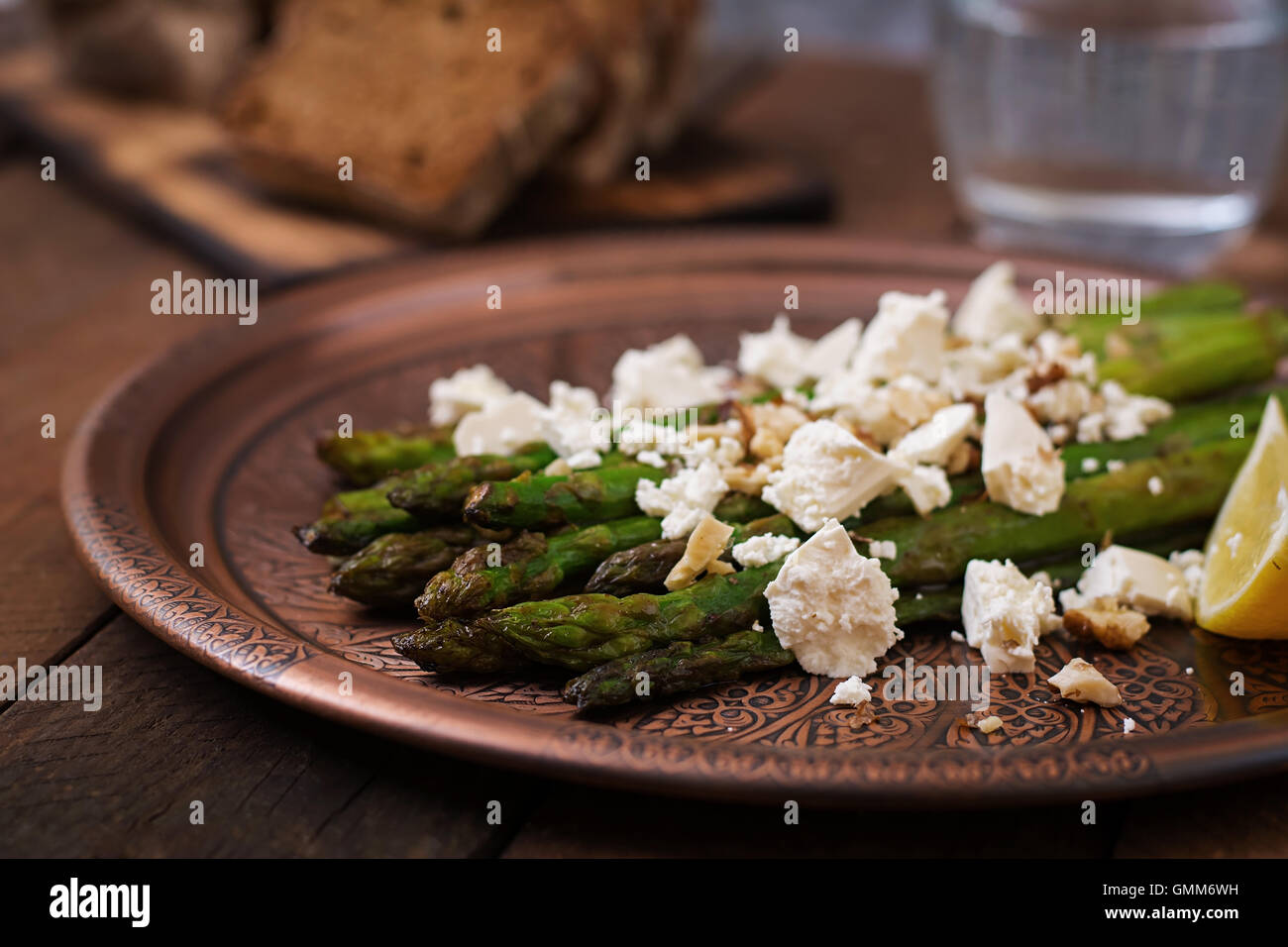 Warm salad of roasted asparagus, feta cheese, nuts, flavored with lemon juice - Stock Image