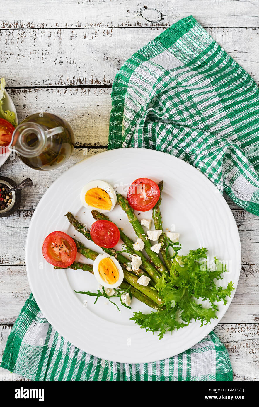 Warm salad of roasted asparagus, feta cheese, tomatoes and eggs. Top view - Stock Image