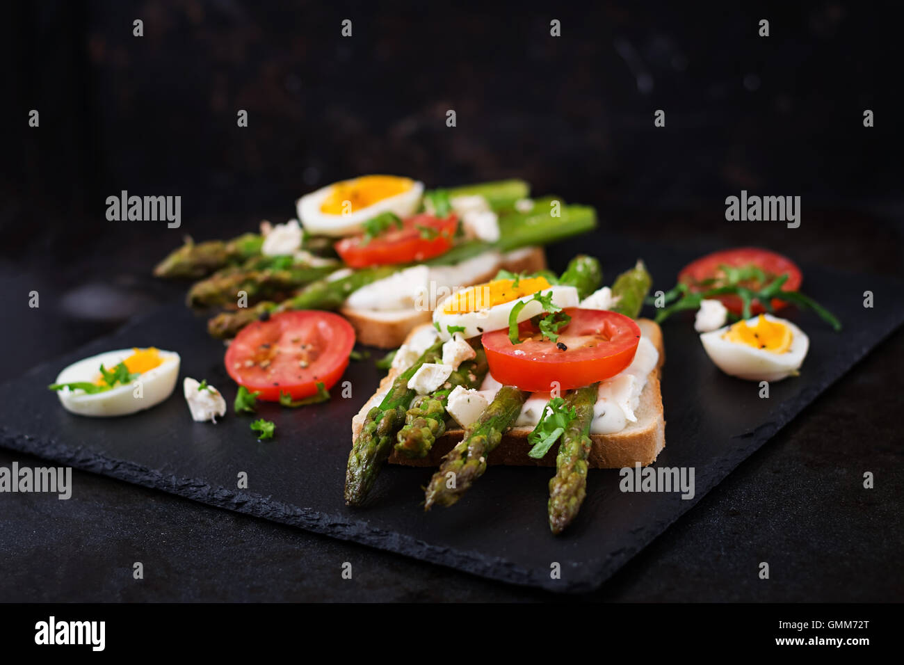 Sandwiches with caramelized asparagus, feta cheese, tomatoes and eggs. - Stock Image