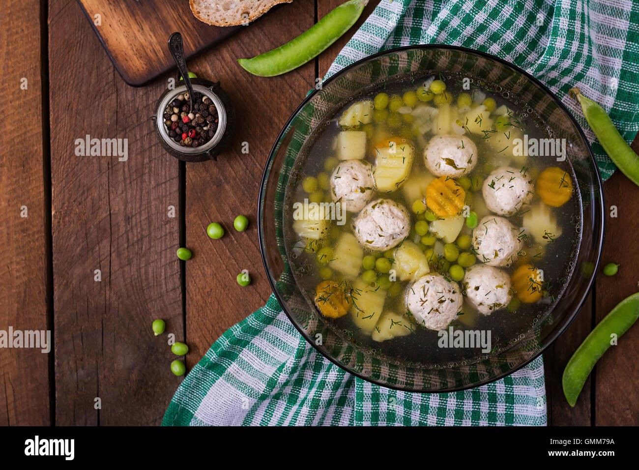 Dietary soup with chicken meatballs and green peas in a glass bowl on a wooden background. Top view - Stock Image