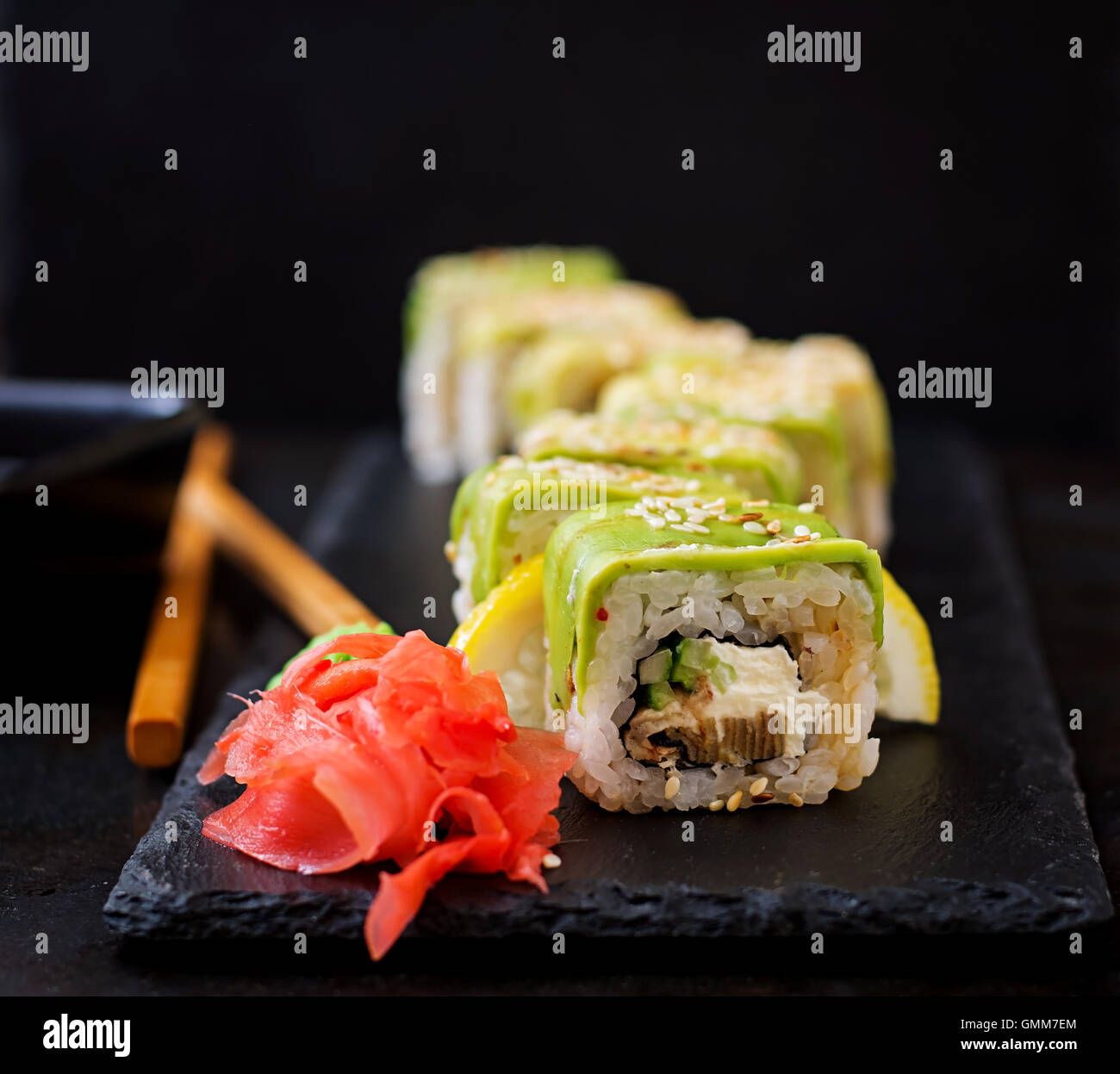 Traditional Japanese food - sushi, rolls and sauce on a black background. - Stock Image