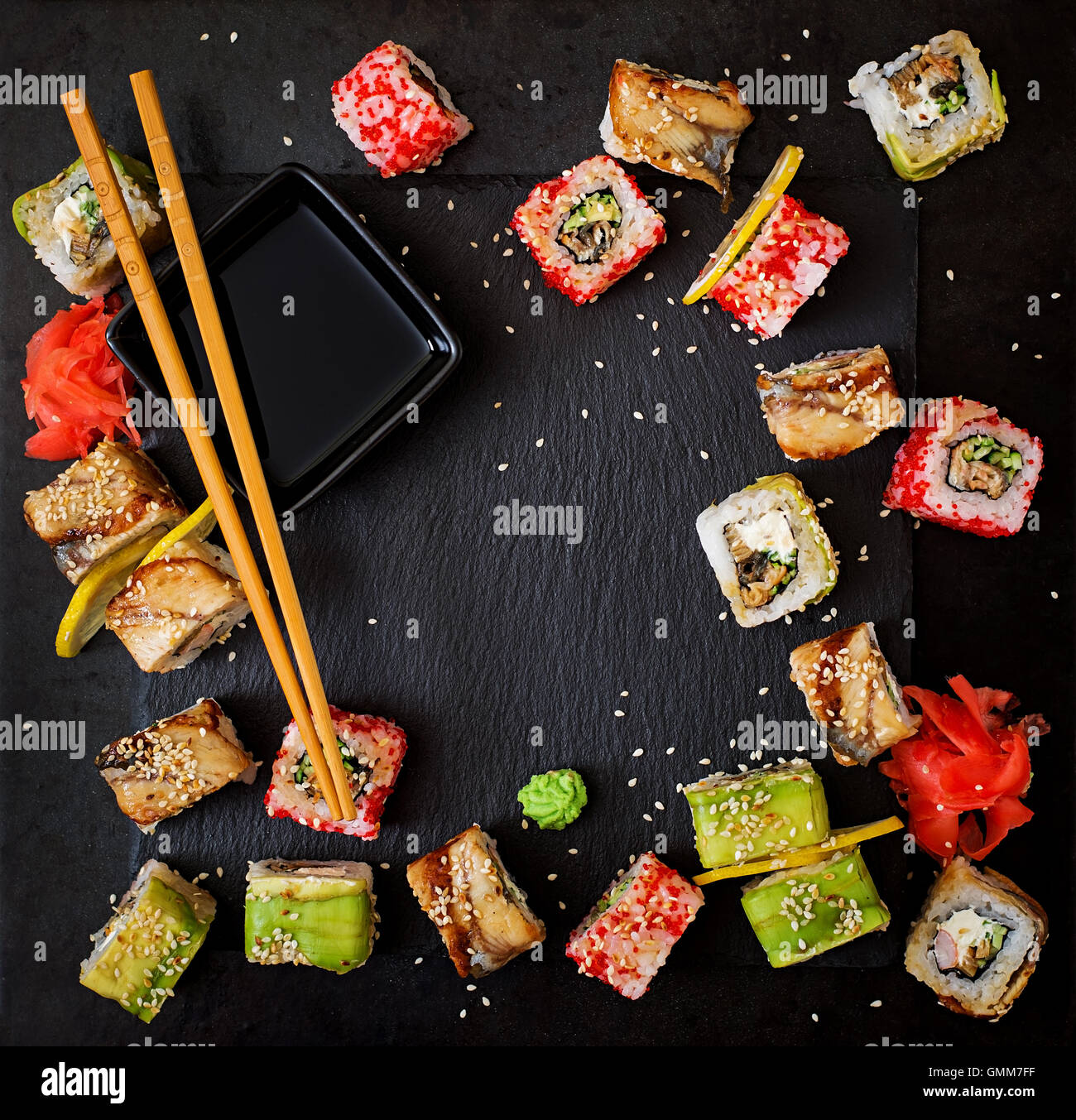 Traditional Japanese food - sushi, rolls and sauce on a black background. Top view - Stock Image