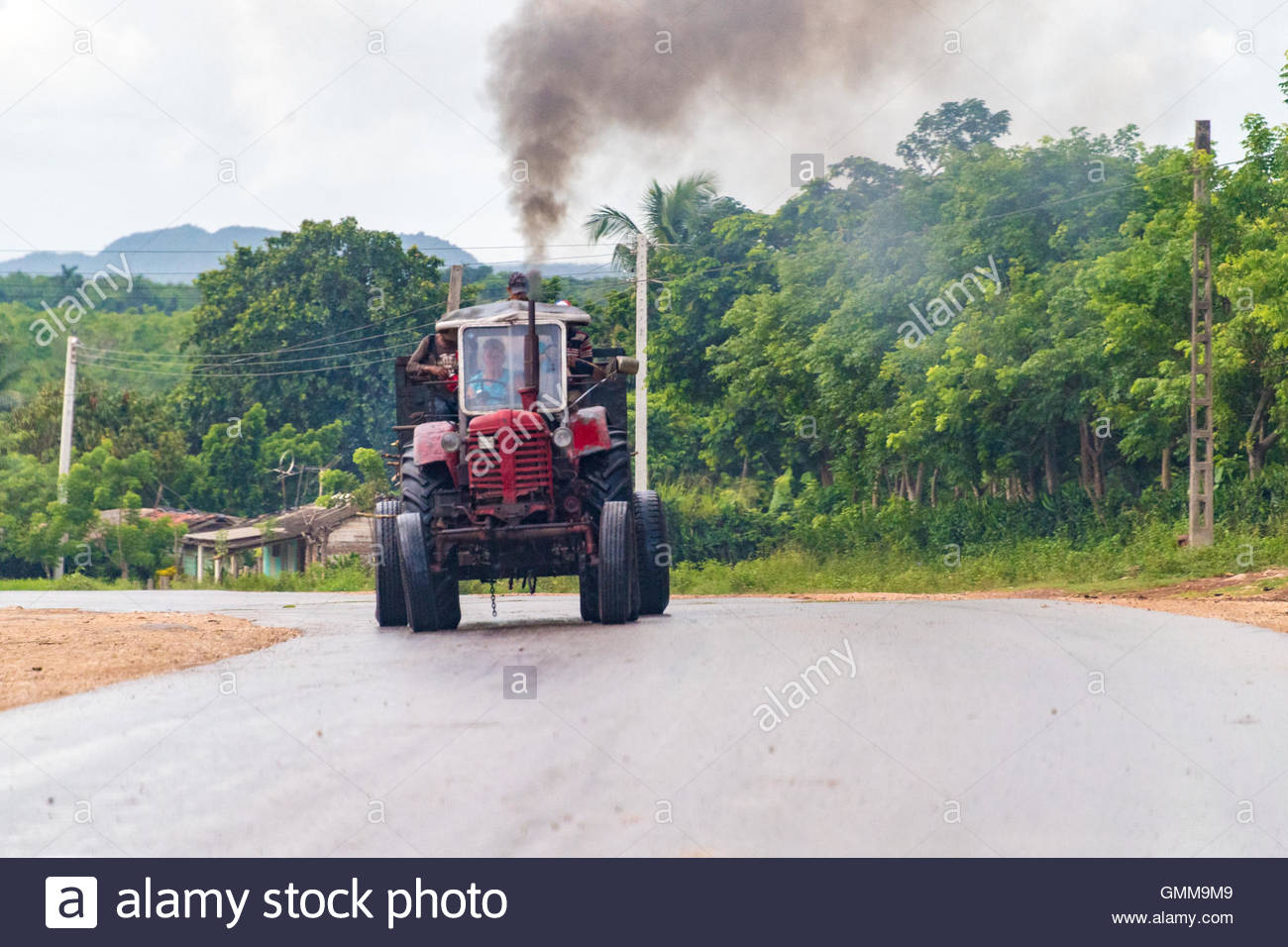 Vintage old Russian agricultural tractor riding on the countryside's main street. - Stock Image
