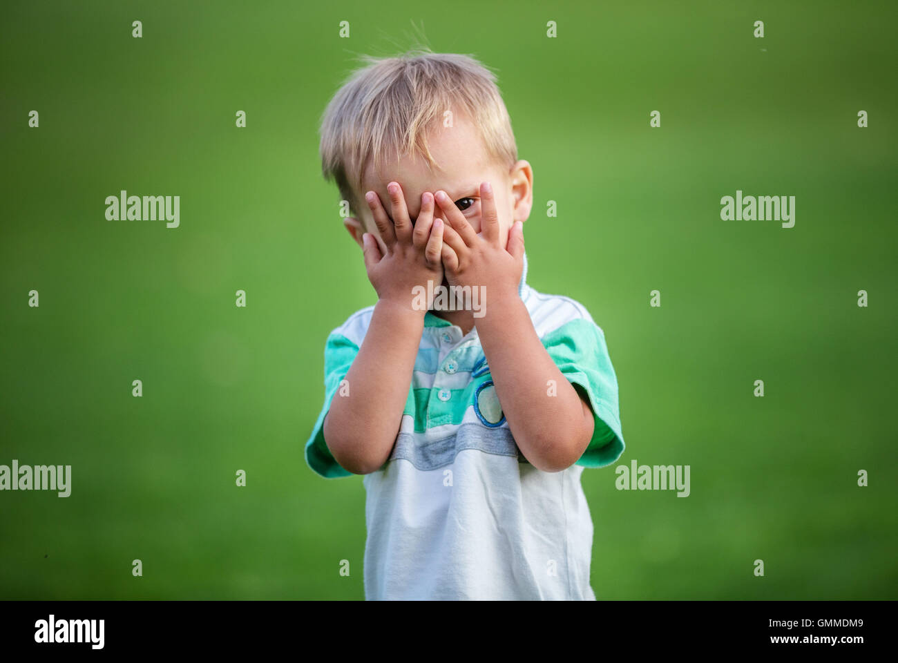 Little boy playing peek-a-boo outdoors - Stock Image