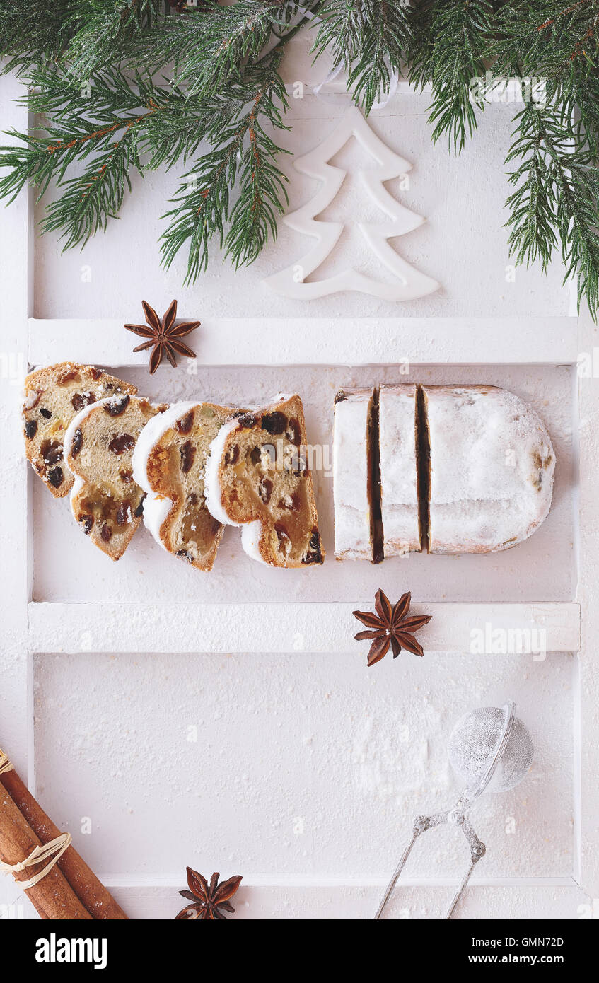 Christmas stollen dusted with icing sugar, partly sliced - Stock Image