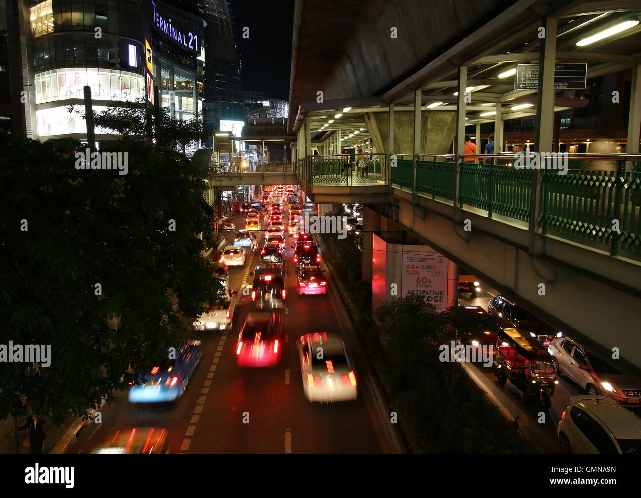 Night scene of the skywalk of Ashok BTS station with the link to Terminal 21, a trendy shopping complex in central - Stock Image
