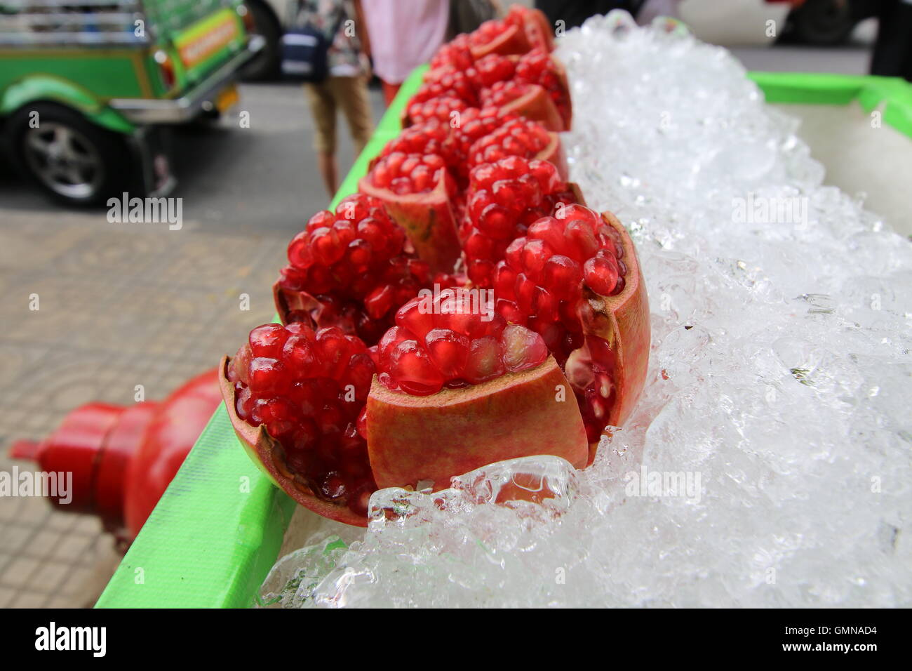 Opened up pomegranate fruit being sold in the street of Bangkok, Thailand - Stock Image