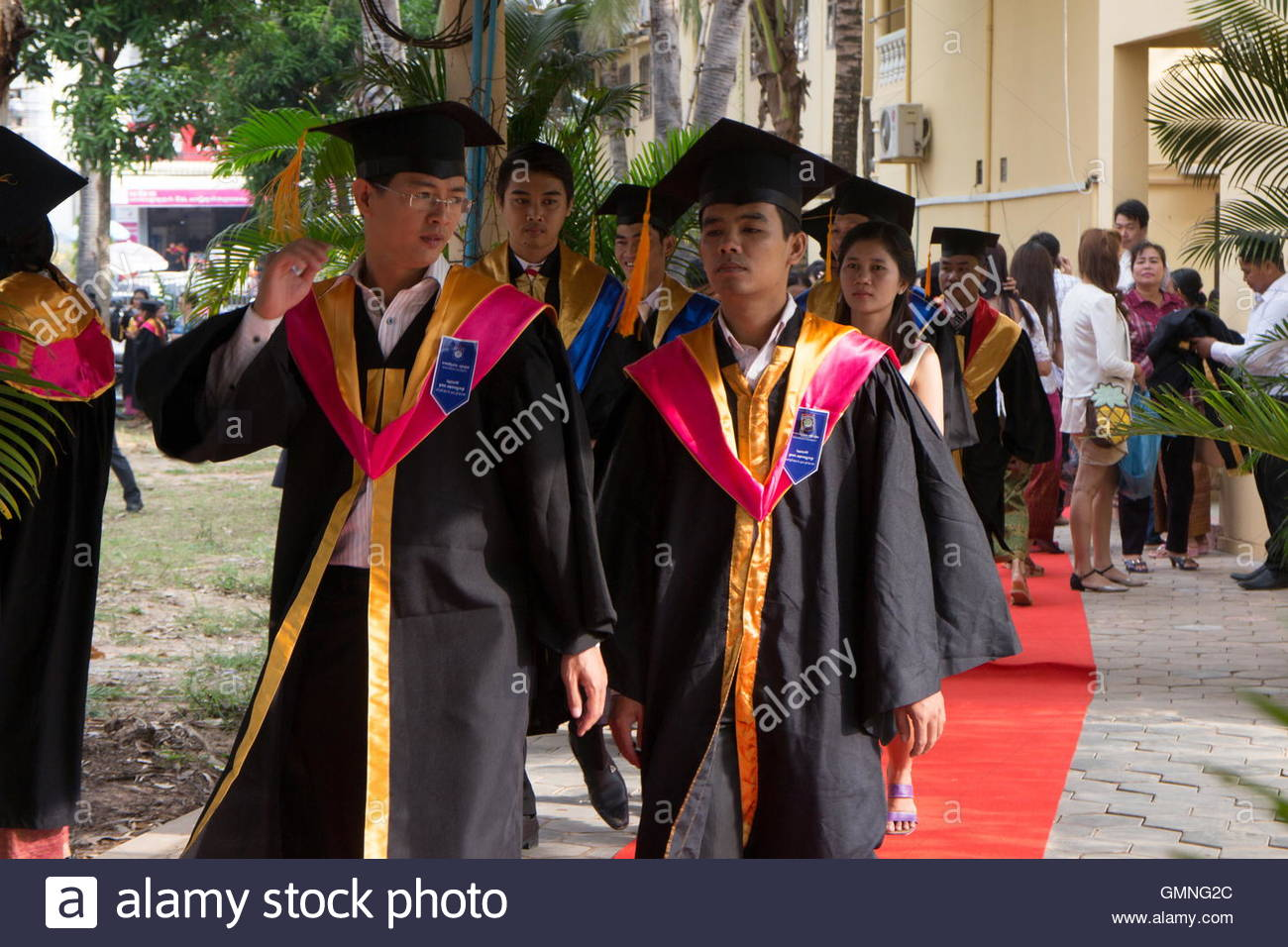Medium view students in Asia arrive at their university graduation ceremony wearing caps and gowns. - Stock Image