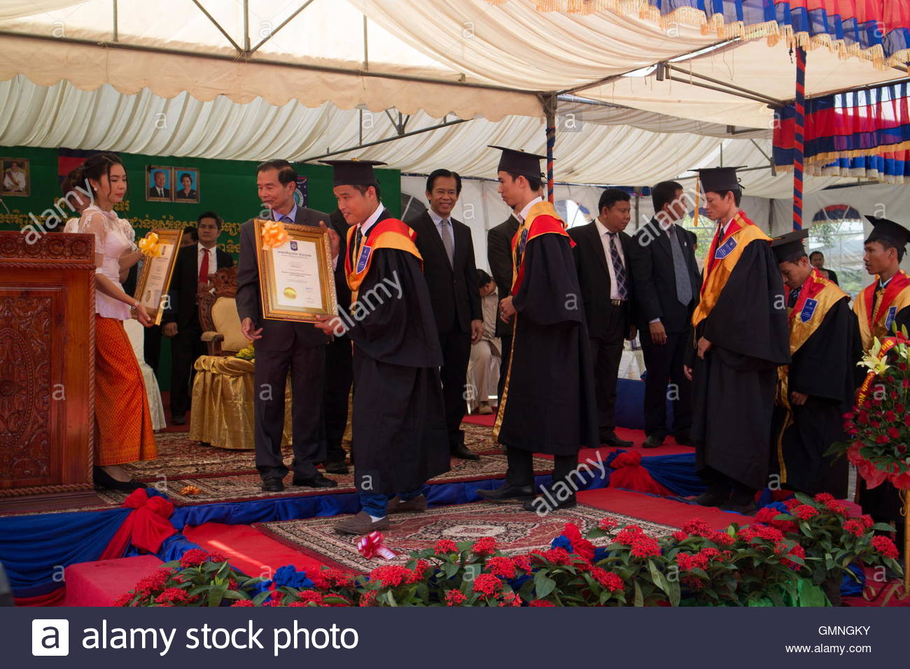 University students in Asia line up to receive their diplomas at a graduation ceremony. - Stock Image