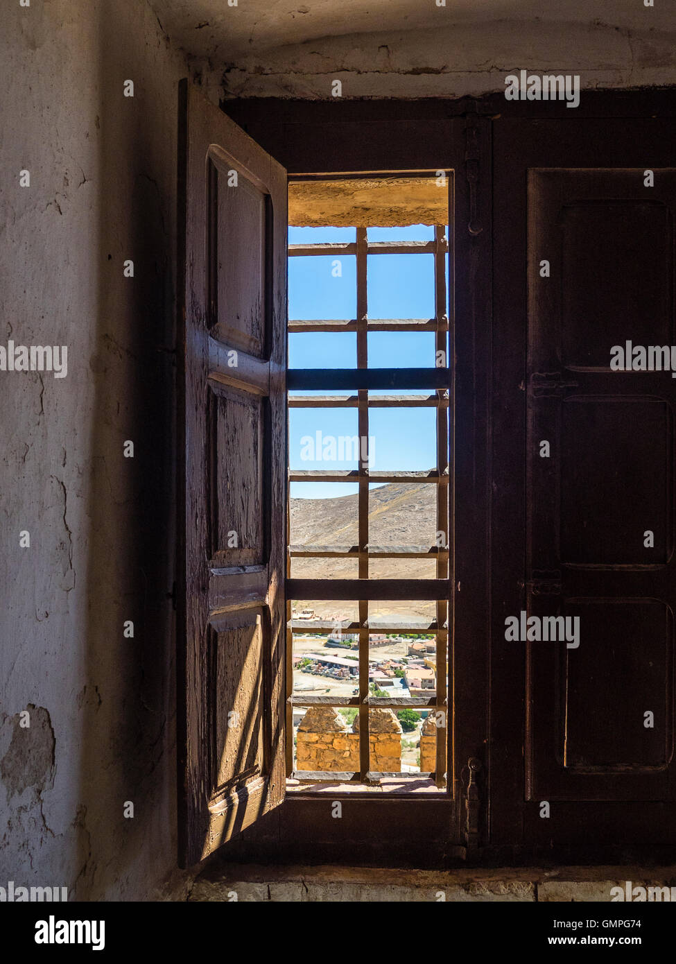 Looking Out An Interior Window With Wooden Shutters And Iron