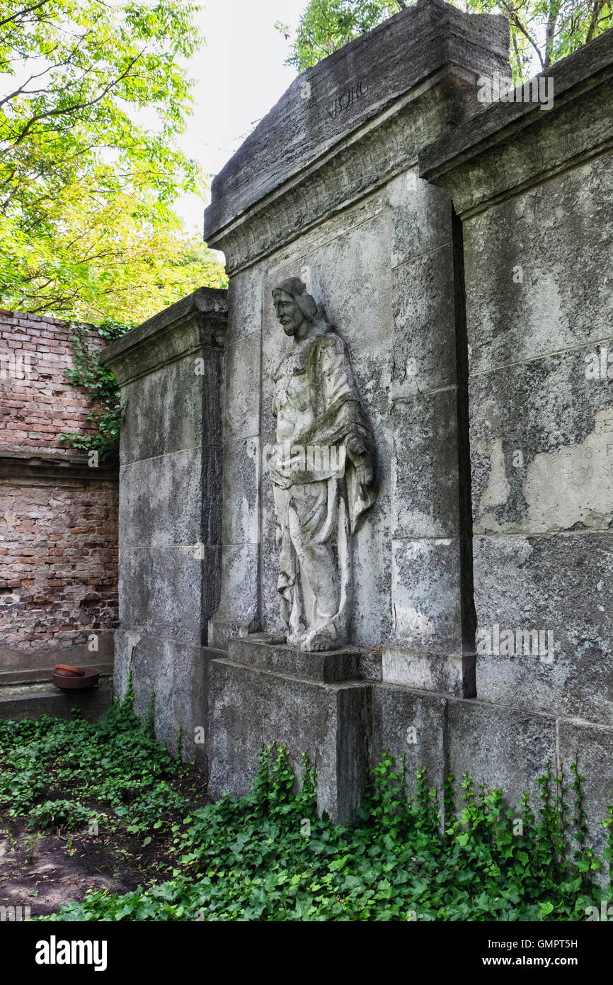 Weathered old tomb memorial with robed man sculpture in the St. Hedwig Cemetery, Alter Domfriedhof St. Hedwig, Berlin. - Stock Image