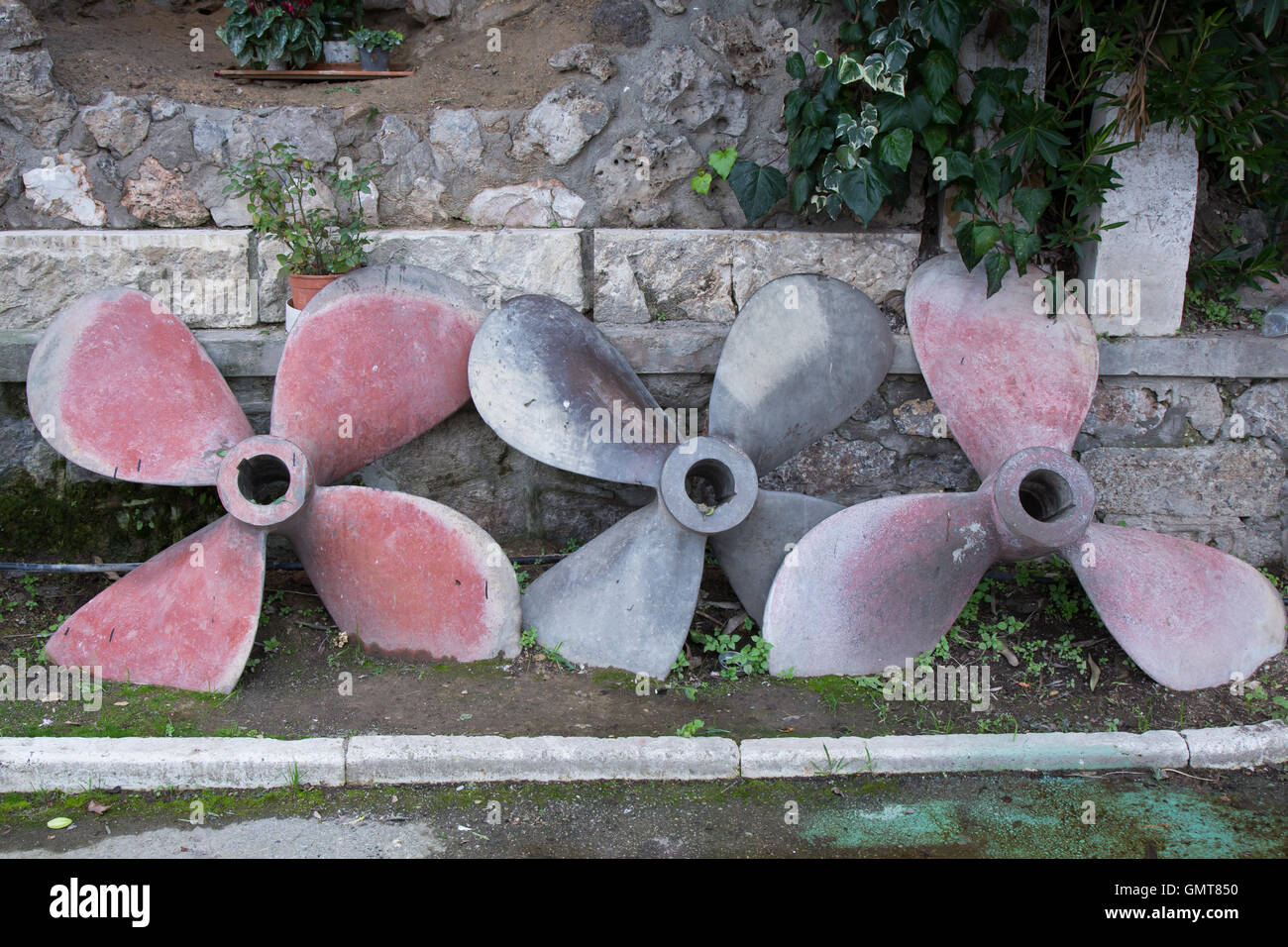 Three ship propellers placed an old wall - Stock Image