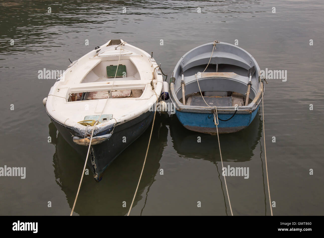 Two fishing boats anchored with ropes - Stock Image