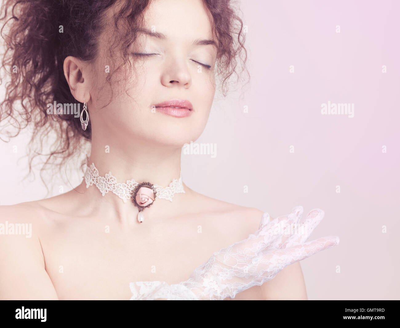 Closeup face portrait of young beautiful woman wearing a lace choker with pink rose and white lacy gloves on pink Stock Photo