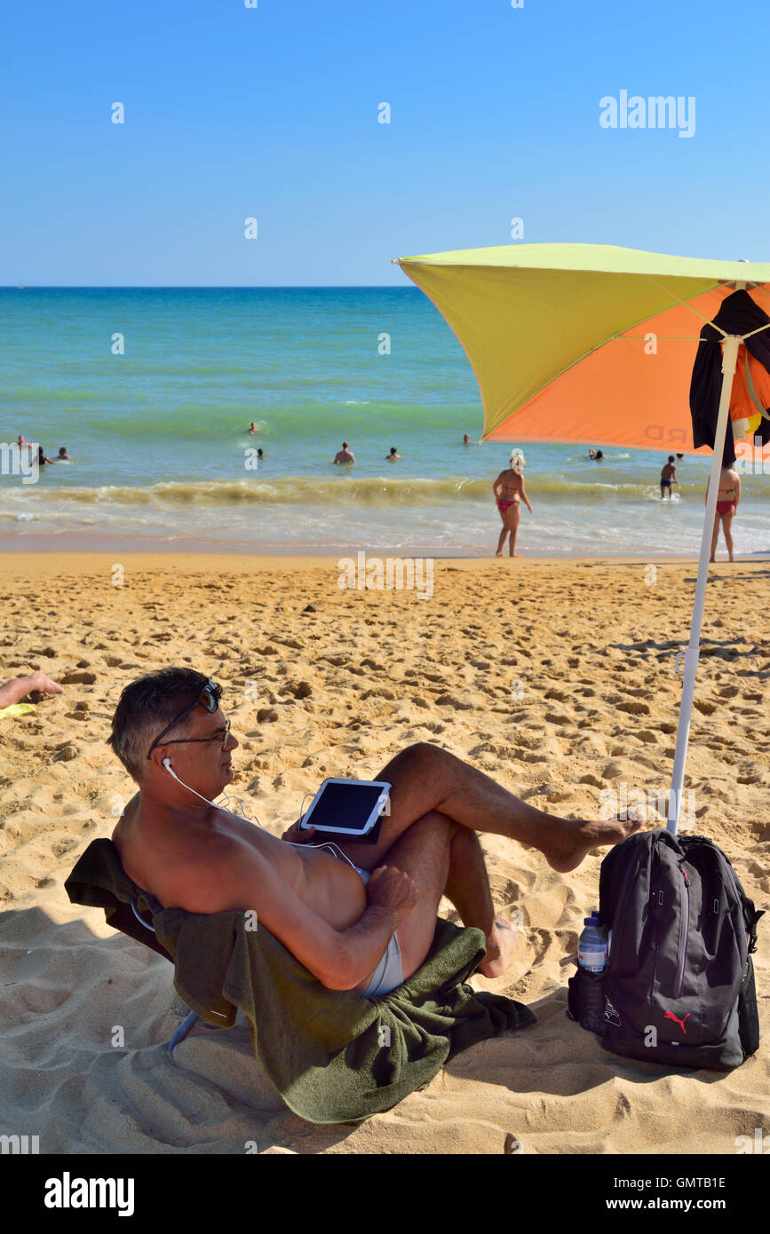 Man with tablet computer and headphones at seaside on sandy beach under umbrella in shade - Stock Image
