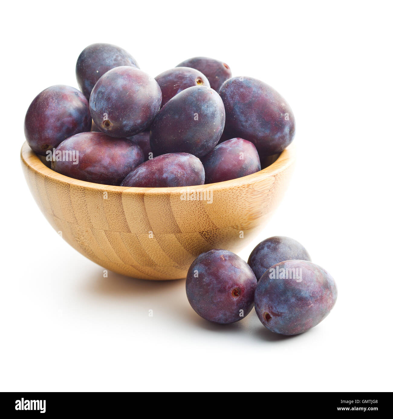 Fresh plums from garden in wooden bowl isolated on white background. - Stock Image