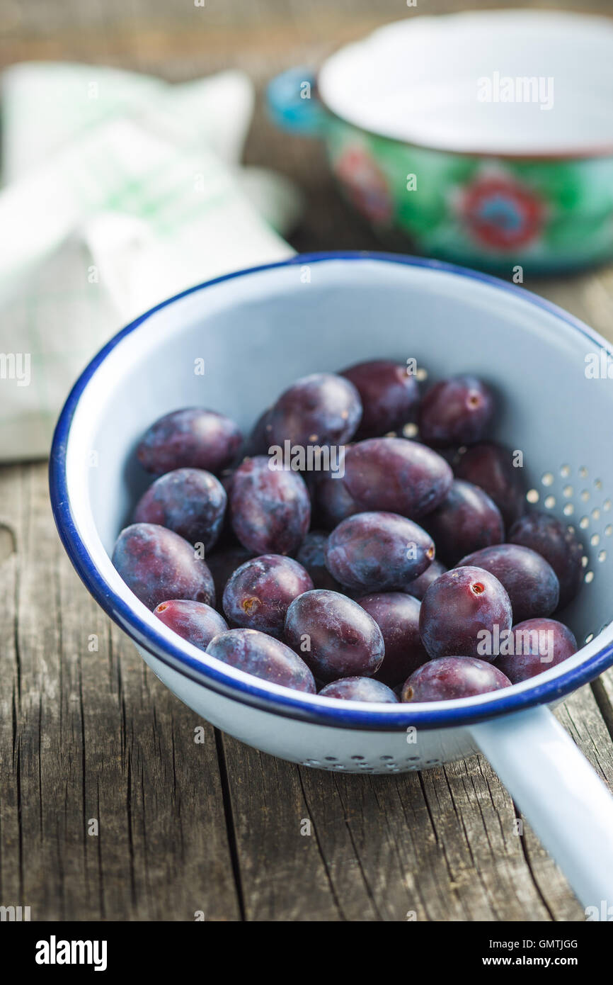 Fresh plums from garden in colander on old wooden table. - Stock Image