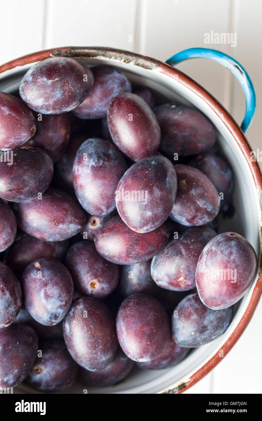 Fresh plums from garden in bowl on old wooden table. Top view. - Stock Image