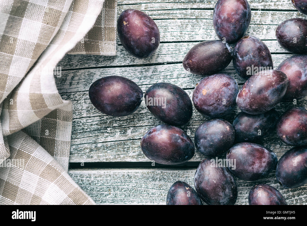 Fresh plums from garden on old kitchen table. Top view. - Stock Image