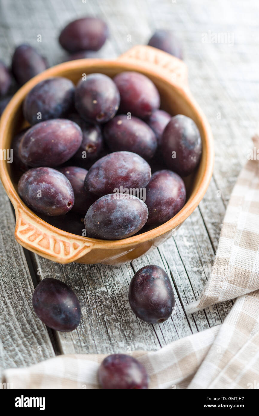 Fresh plums from garden in bowl on old wooden table. - Stock Image