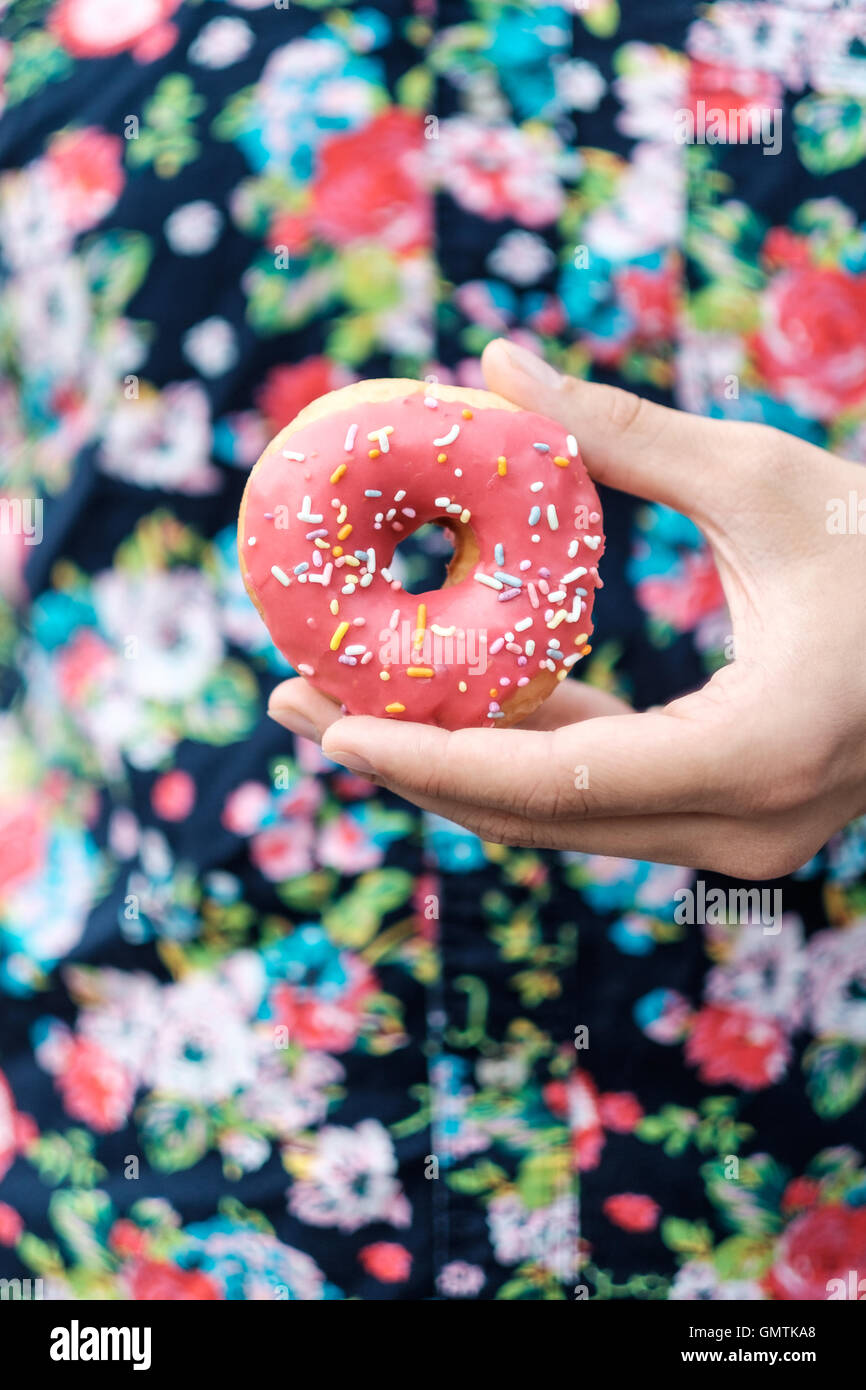 Hand holding a pink sprinkle donut against a floral button up pattern shirt. - Stock Image