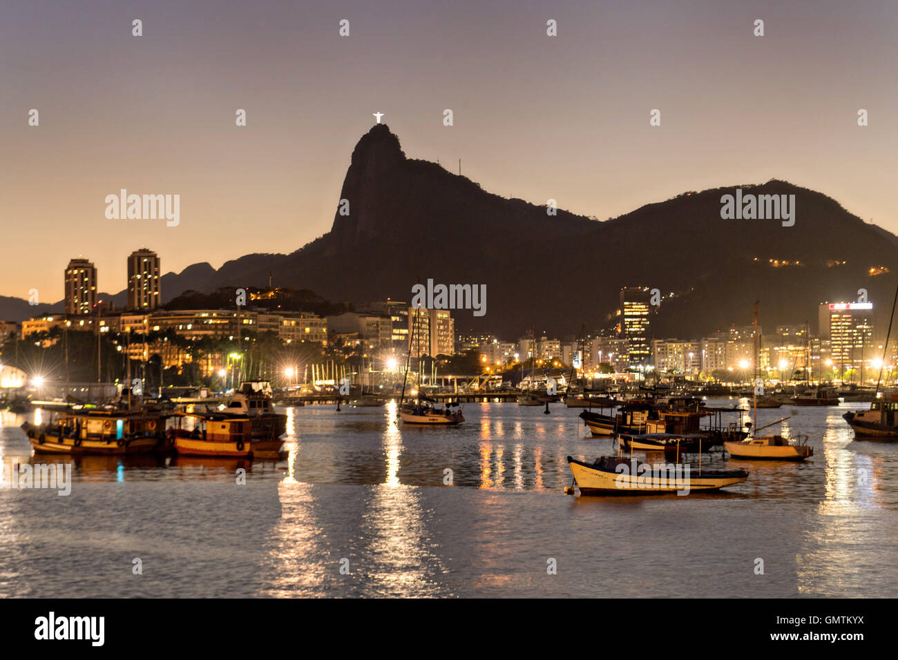 Christ the Redeemer statue is lighted at twilight across seen from across Guanabara Bay at the Urca neighborhood Stock Photo