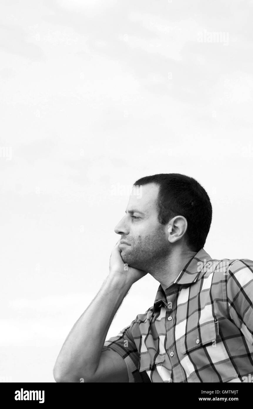 Black and white photo of a man looking out with his face leaning against his hand wearing a plaid shirt. - Stock Image