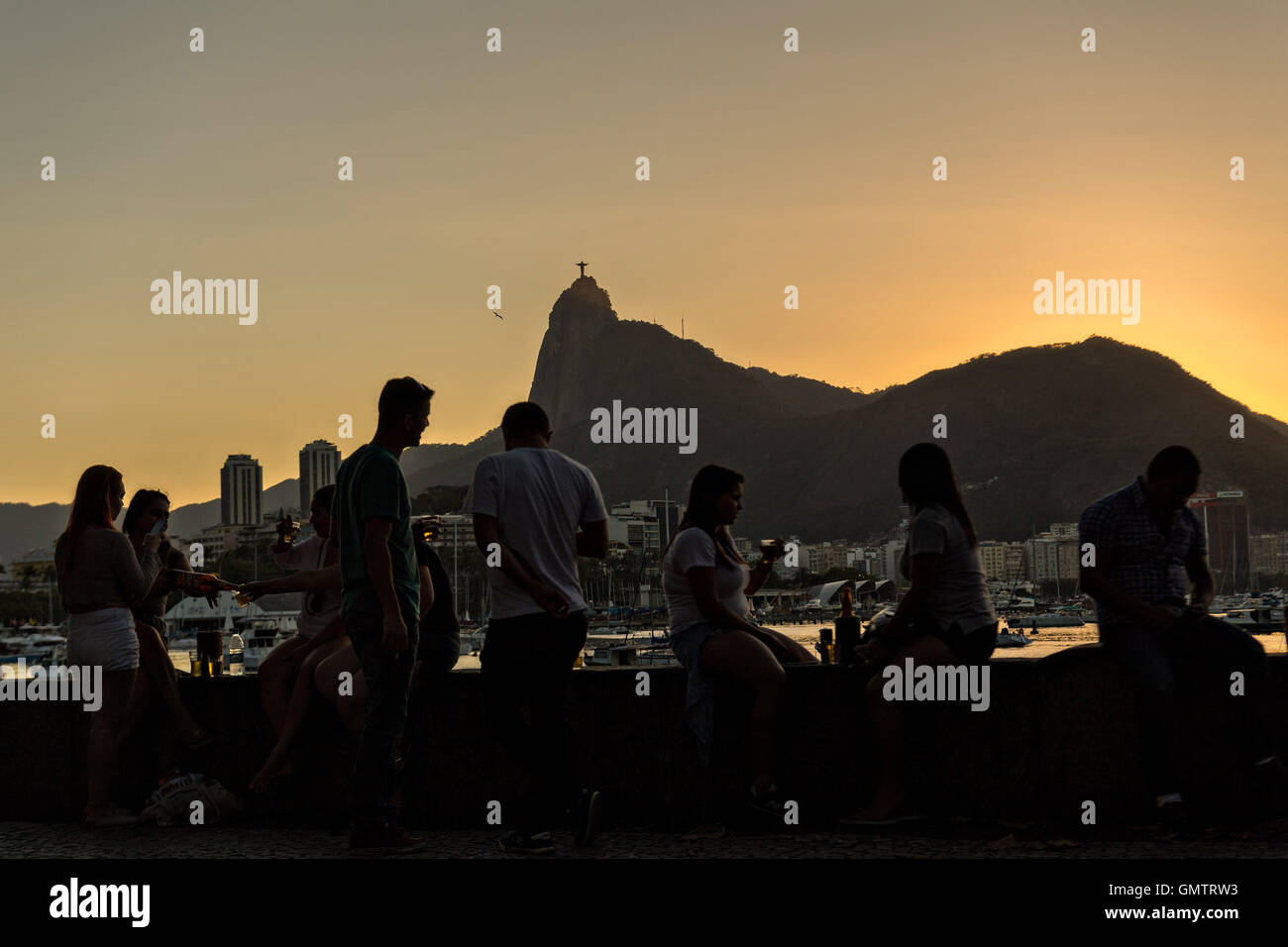 Residents gather to watch the sunset over Christ the Redeemer statue along Guanabara Bay at the Urca neighborhood Stock Photo