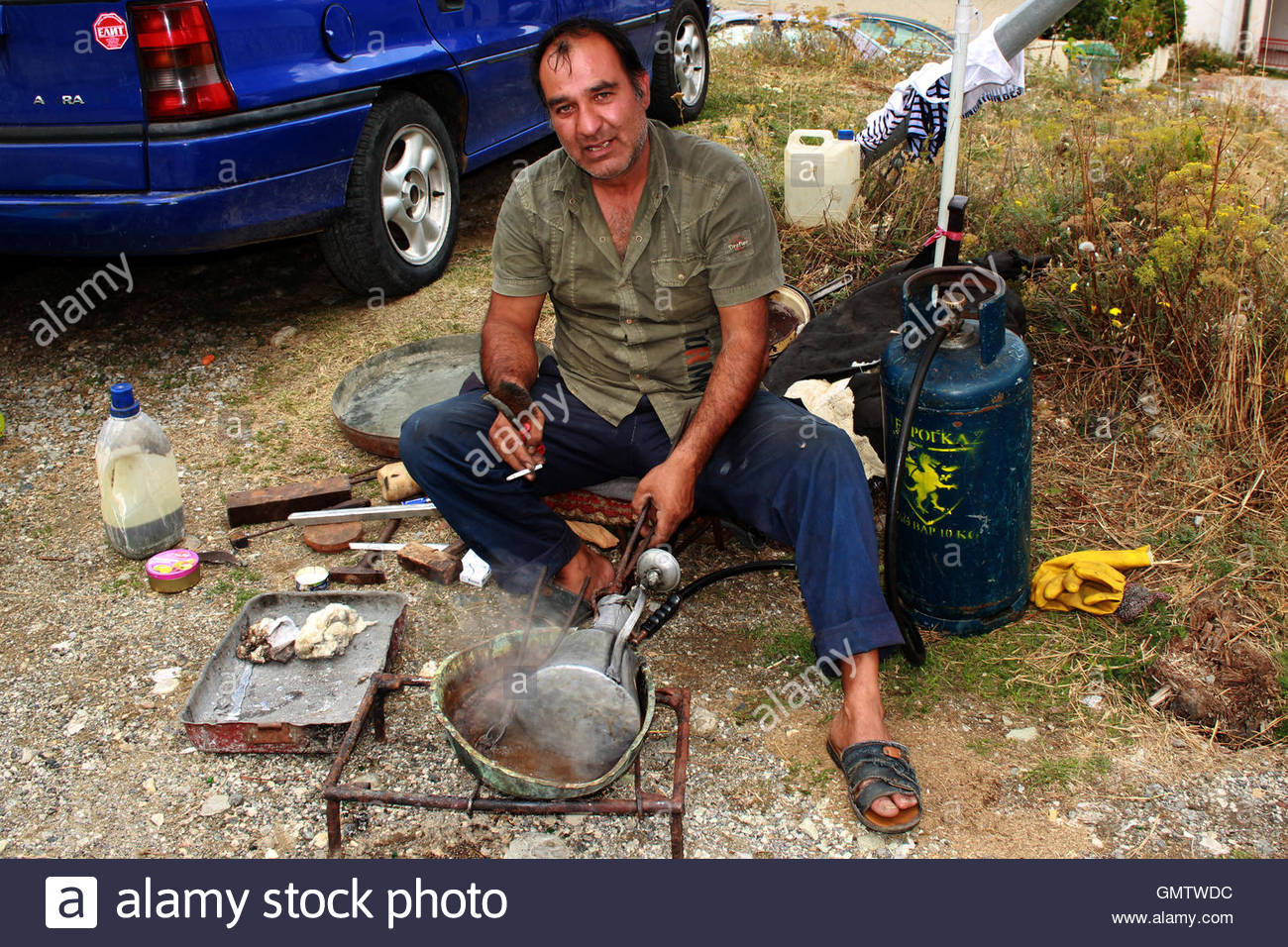 A wandering craftsman is applying melted alloy to bronze cooking pots - Stock Image