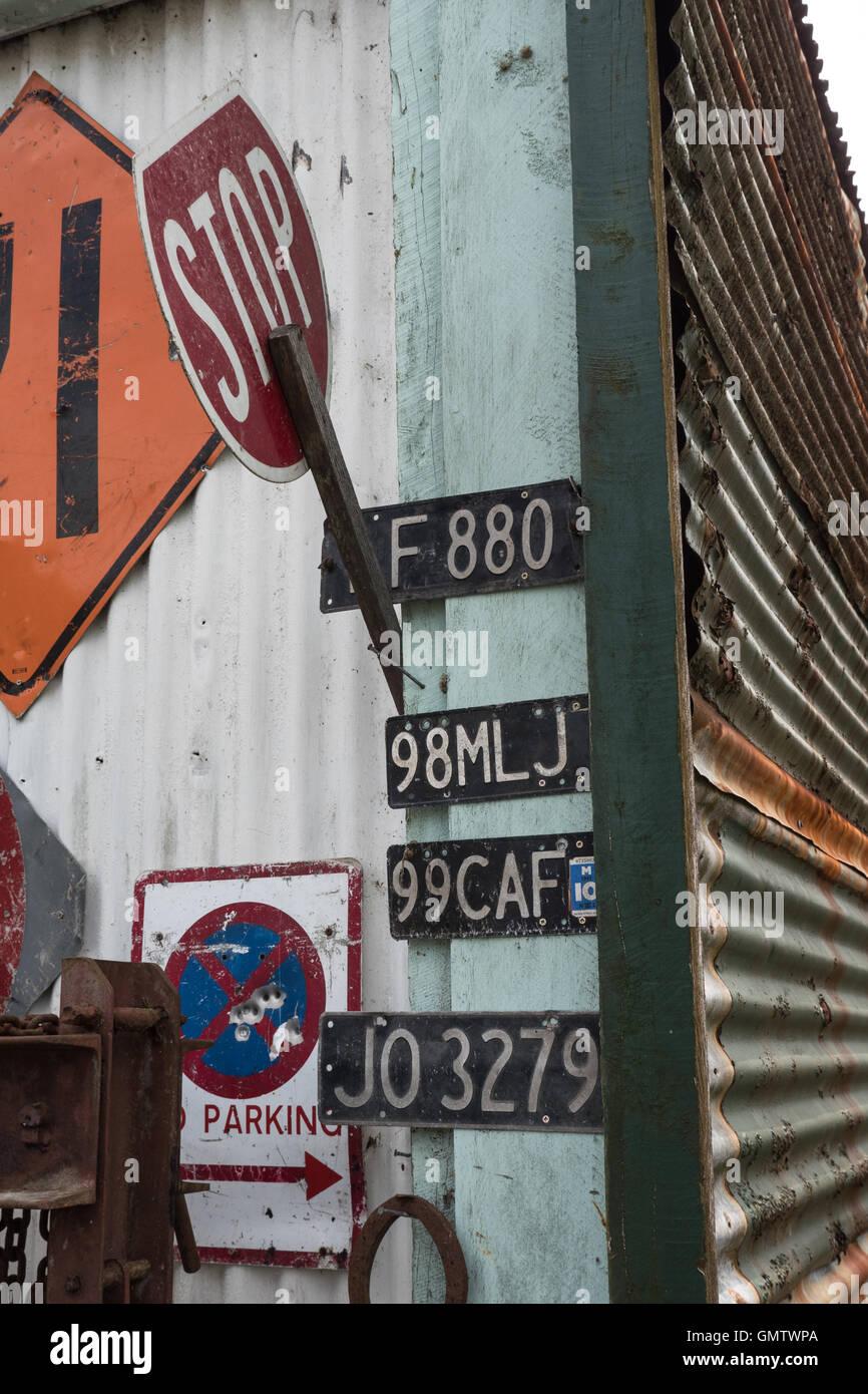 Traffic signs and number plates fixed to an old barn. Whangamomona, Taranaki, North Island, New Zealand. - Stock Image