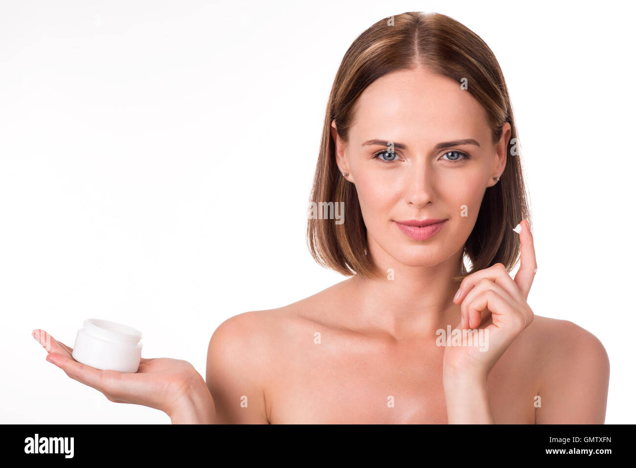 Attractive young woman holding cream - Stock Image