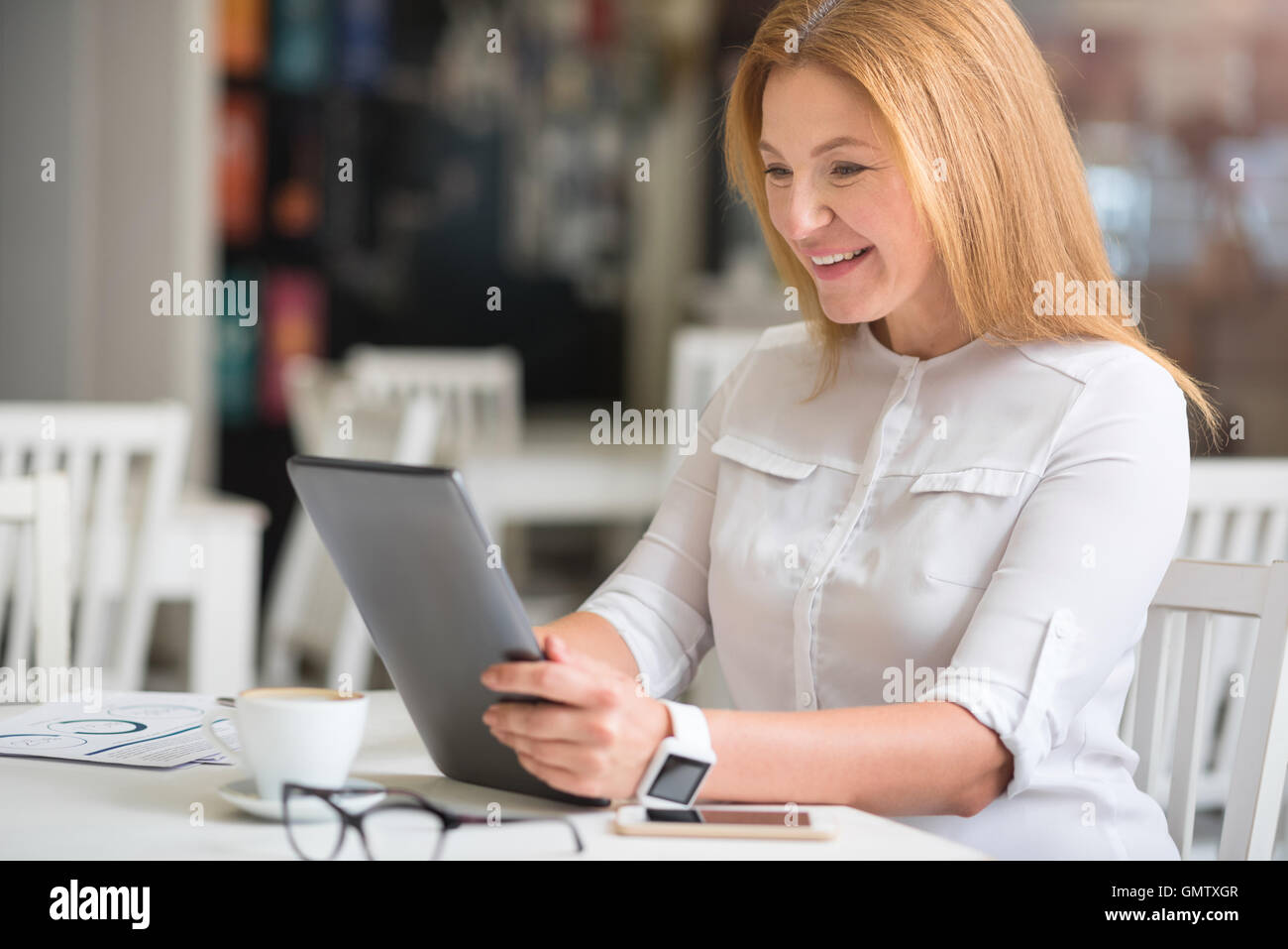 Cheerful woman sitting at the table - Stock Image