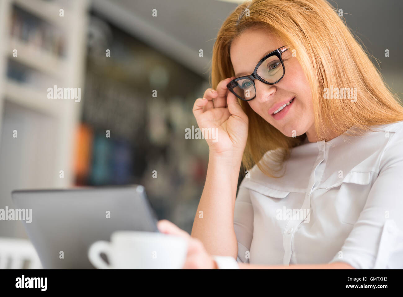 Pleasant smiling woman sitting at the table - Stock Image