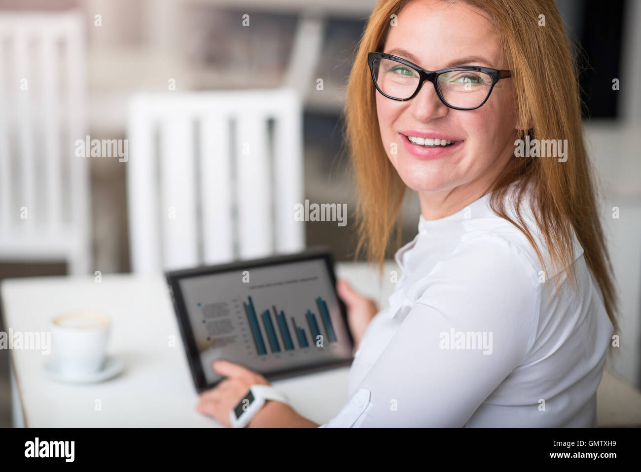 Joyful woman using tablet - Stock Image