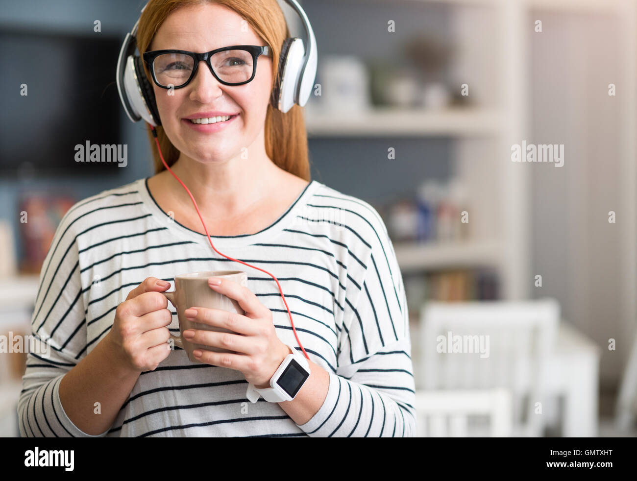 Positive senior woman listening to music - Stock Image