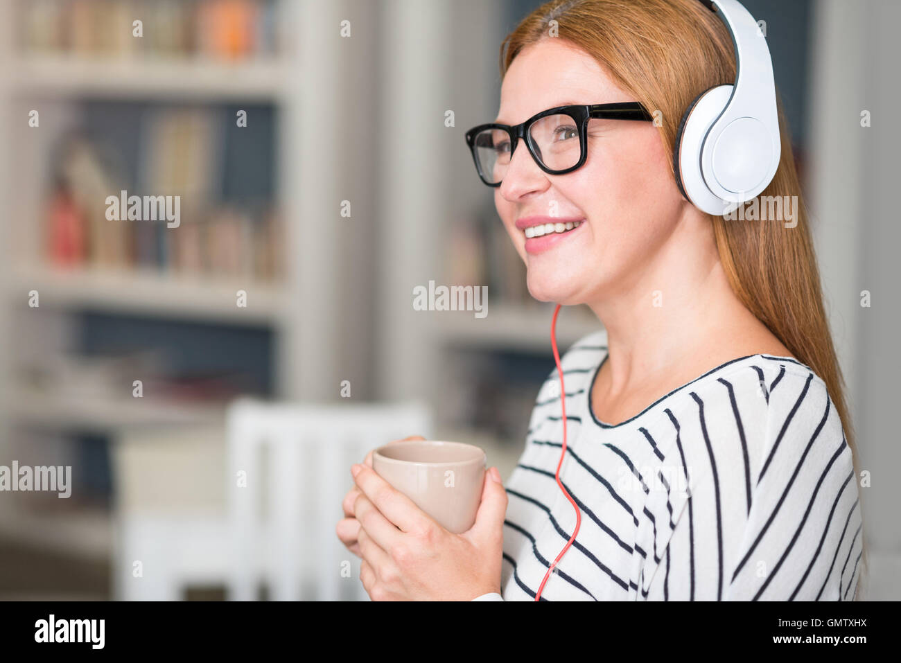 Positive woman listening to music - Stock Image