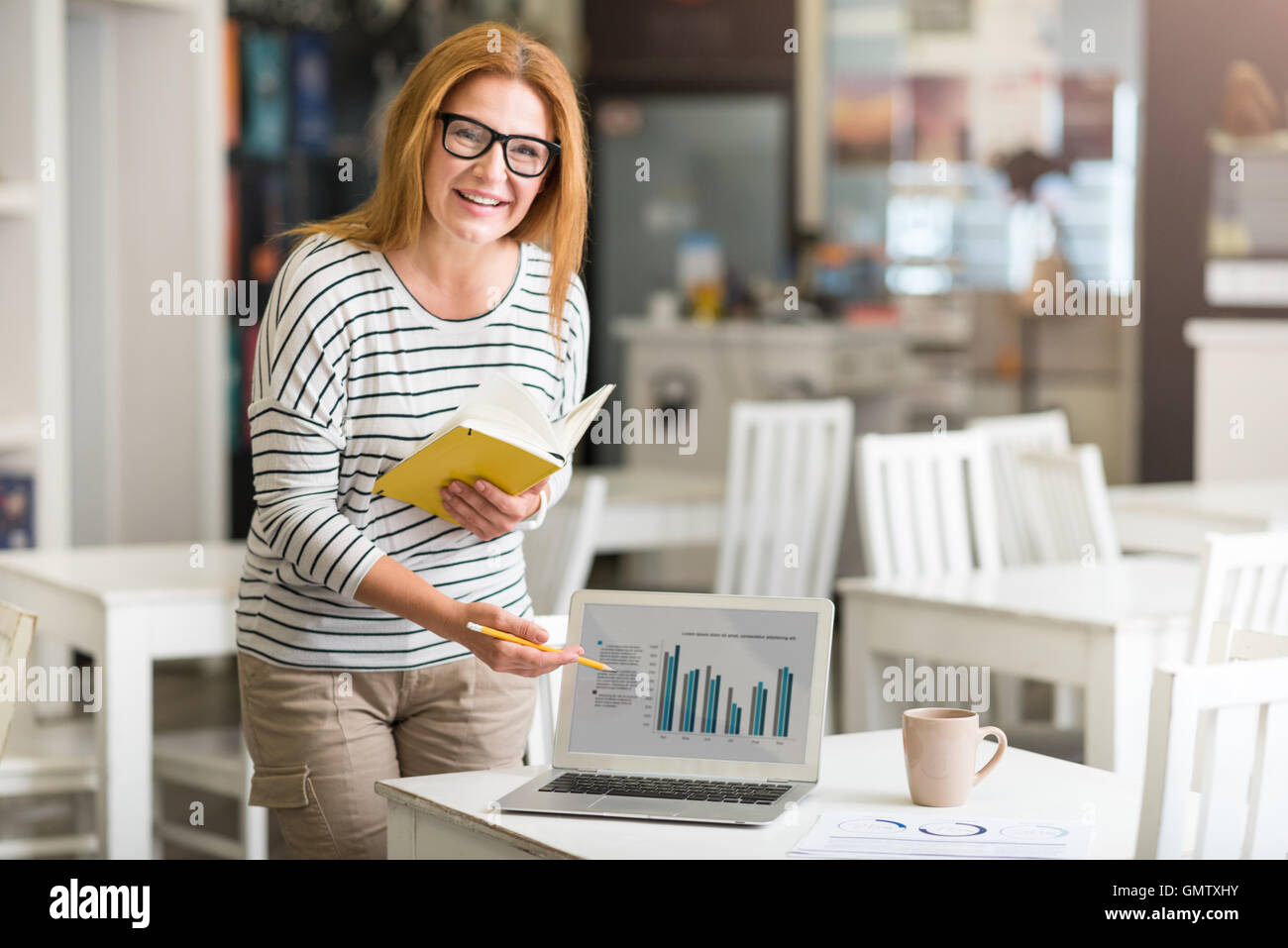 Positive woman working on the project - Stock Image