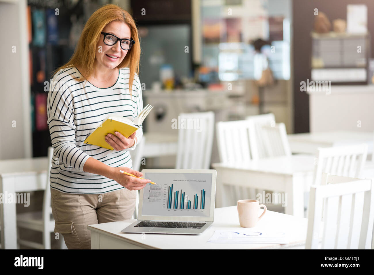 Pleasant positive woman working o the project - Stock Image