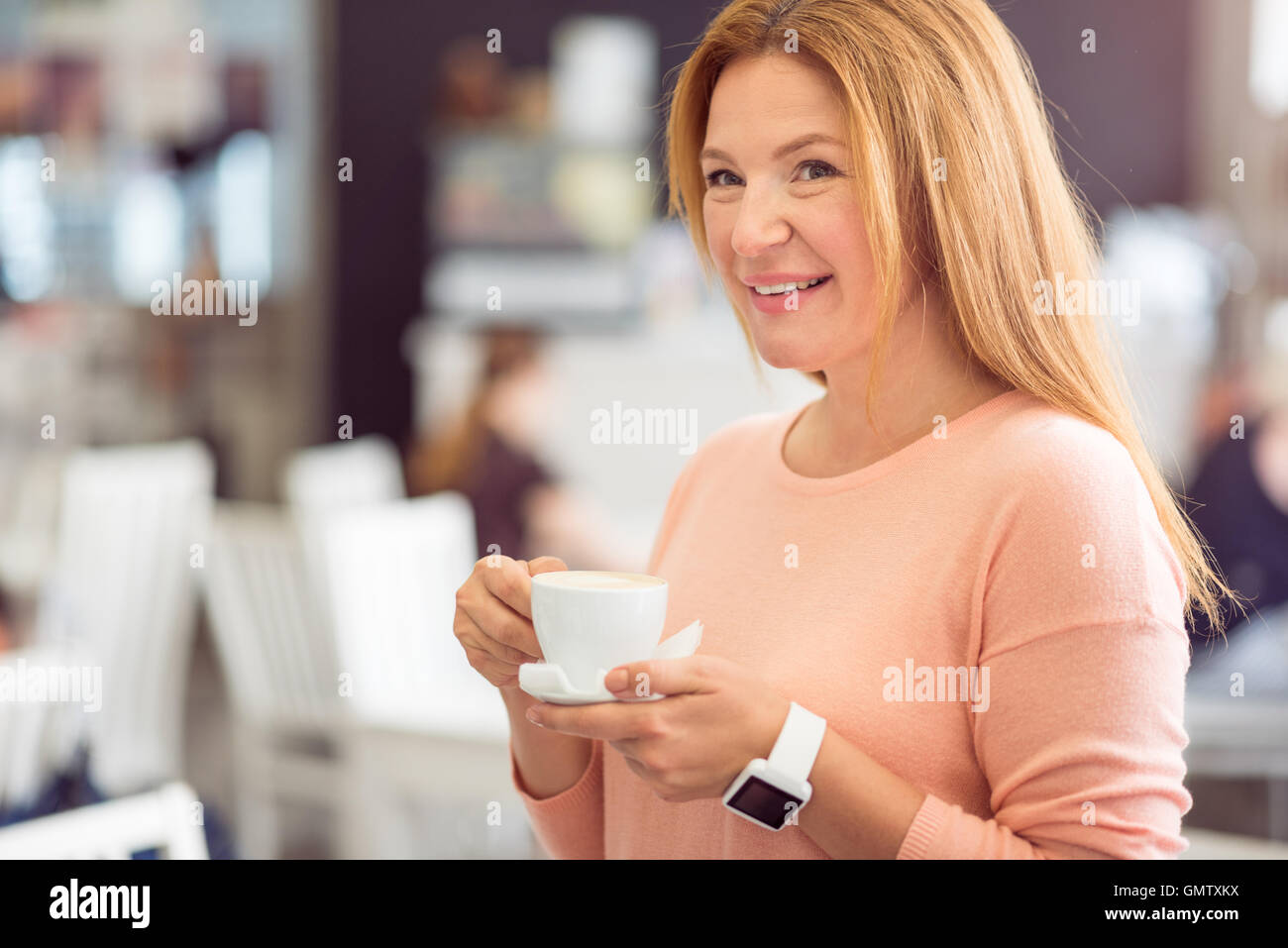 Cheerful woman drinking coffee - Stock Image