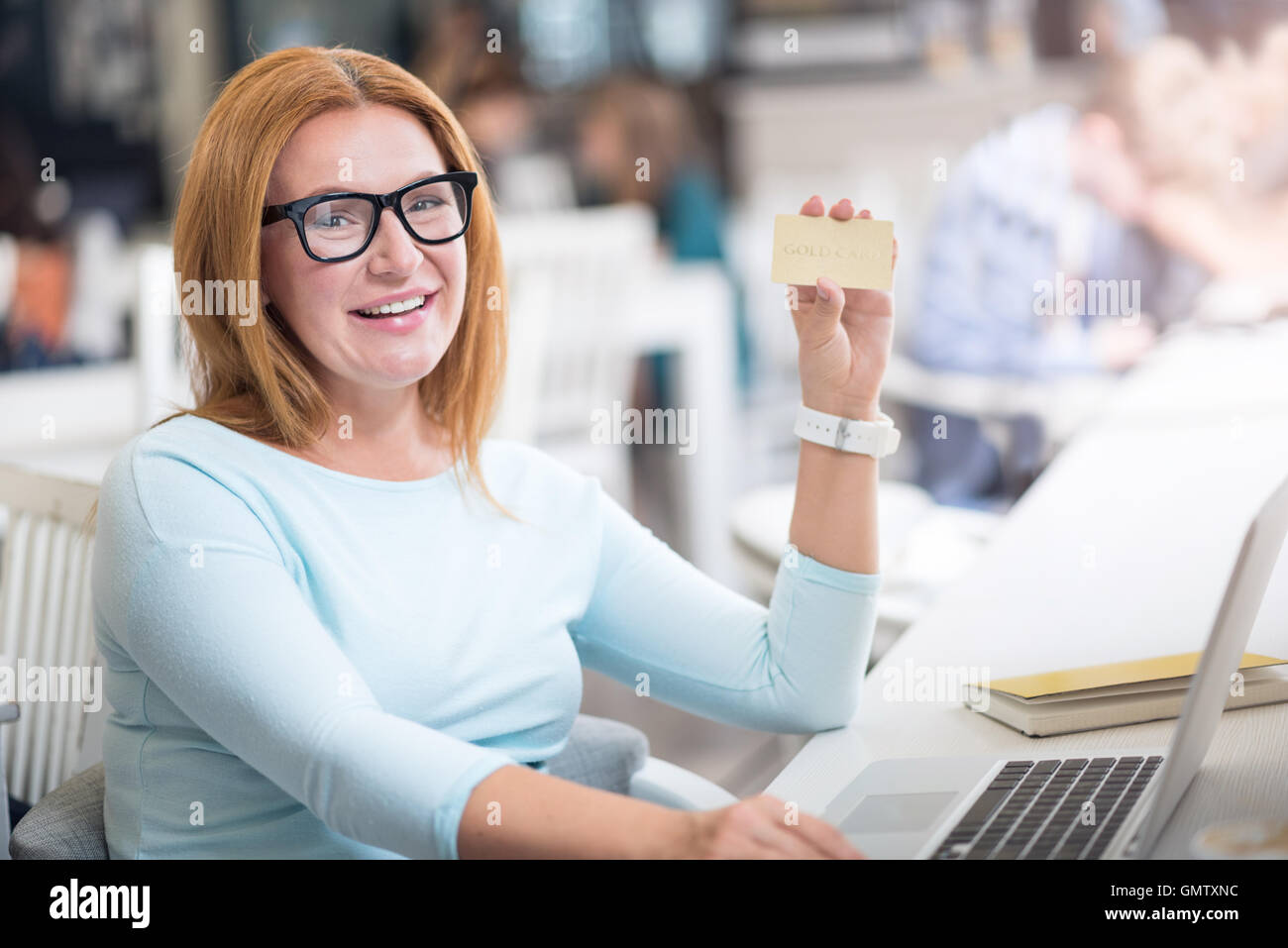 Joyful woman holding gold card - Stock Image