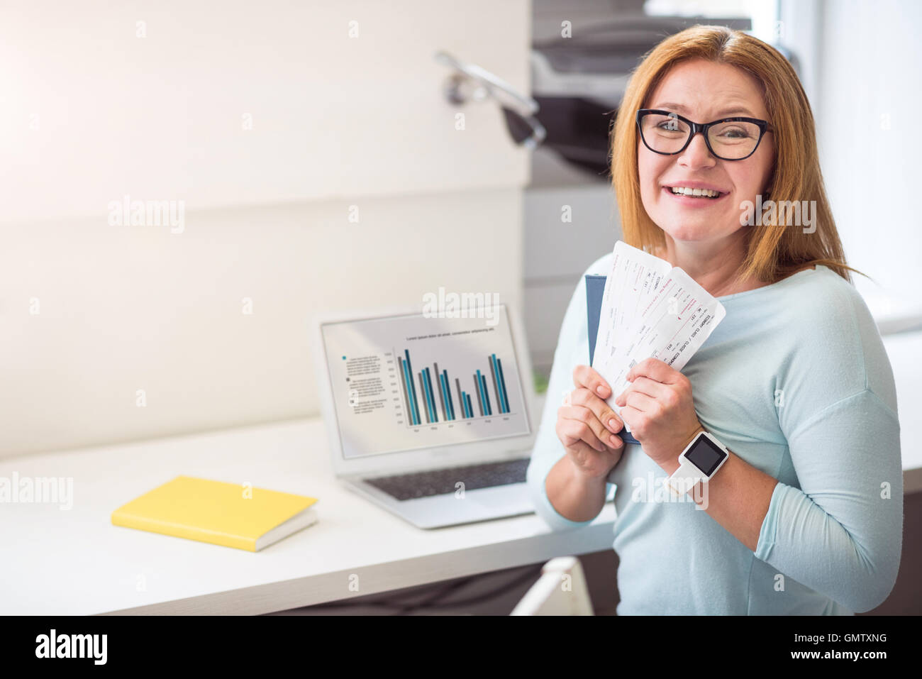 Joyful woman holding tickets. - Stock Image
