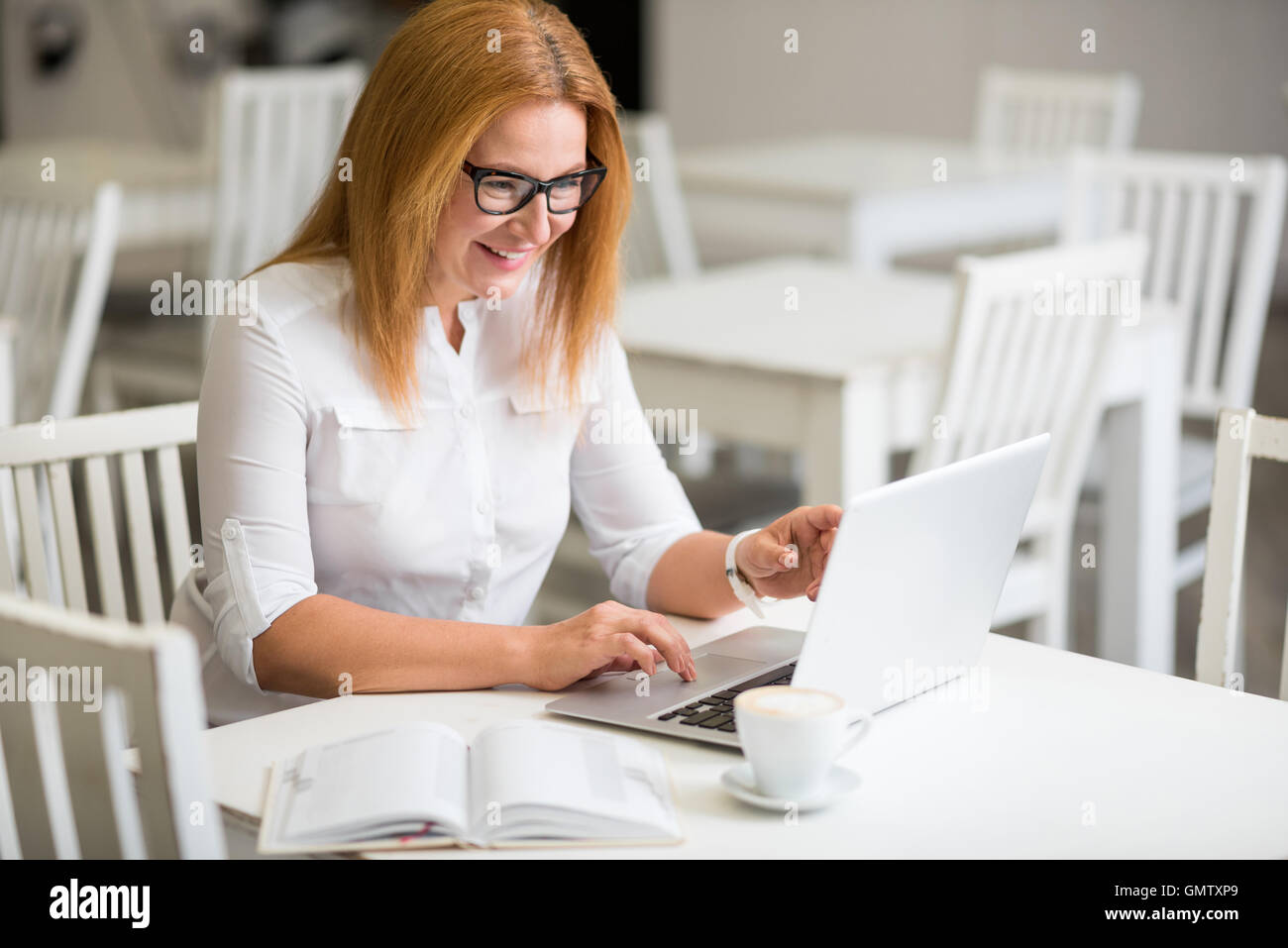 Positive senior woman sitting at the table - Stock Image