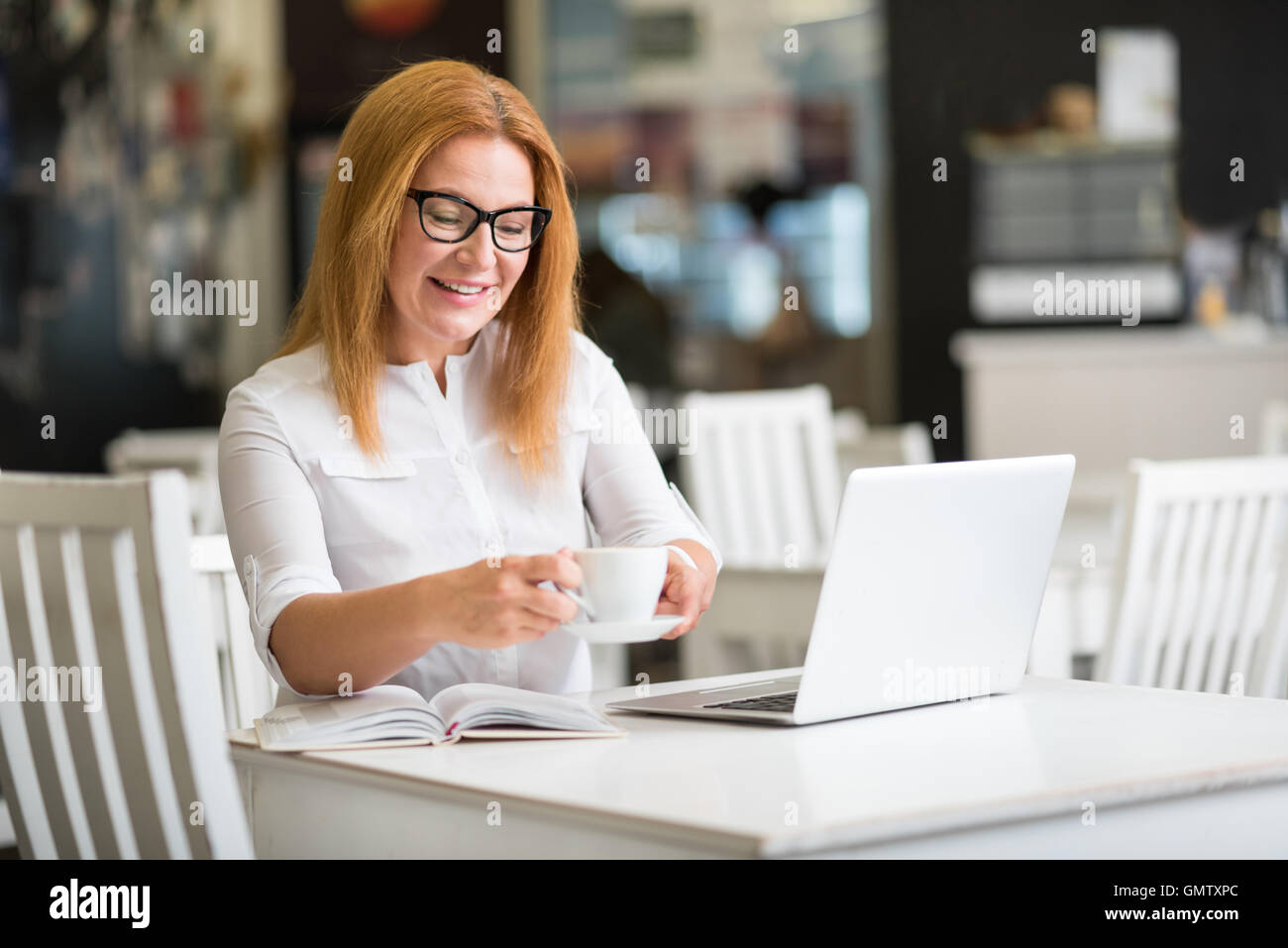 Delighted senior woman resting in the cafe - Stock Image