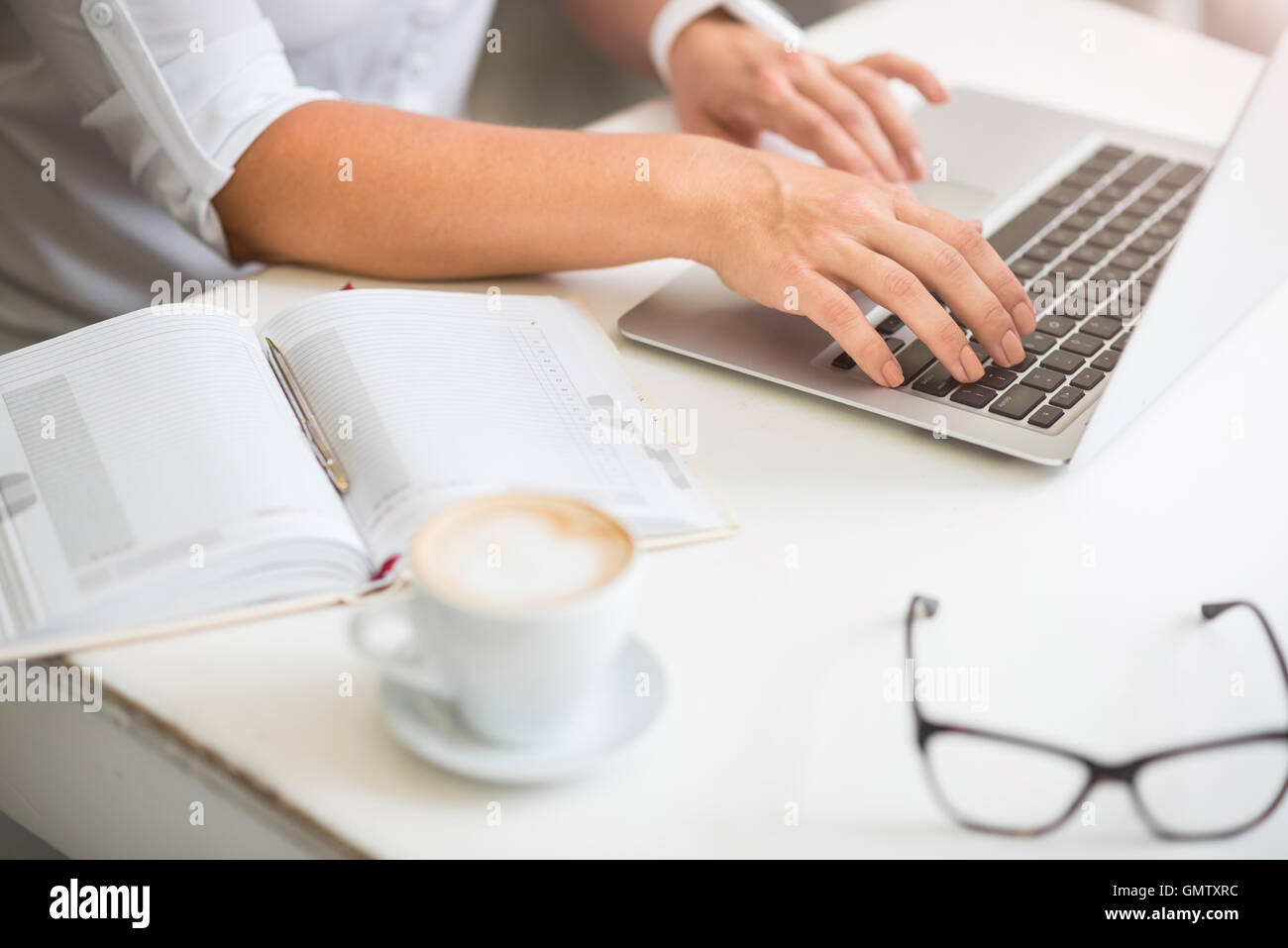 Pleasant woman working on the laptop - Stock Image