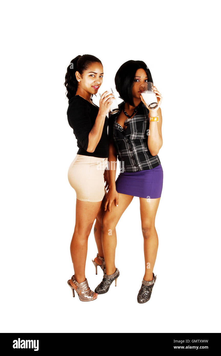 Two young pretty mixed race woman standing for white background drinking a class of milk each, in short skirts. - Stock Image