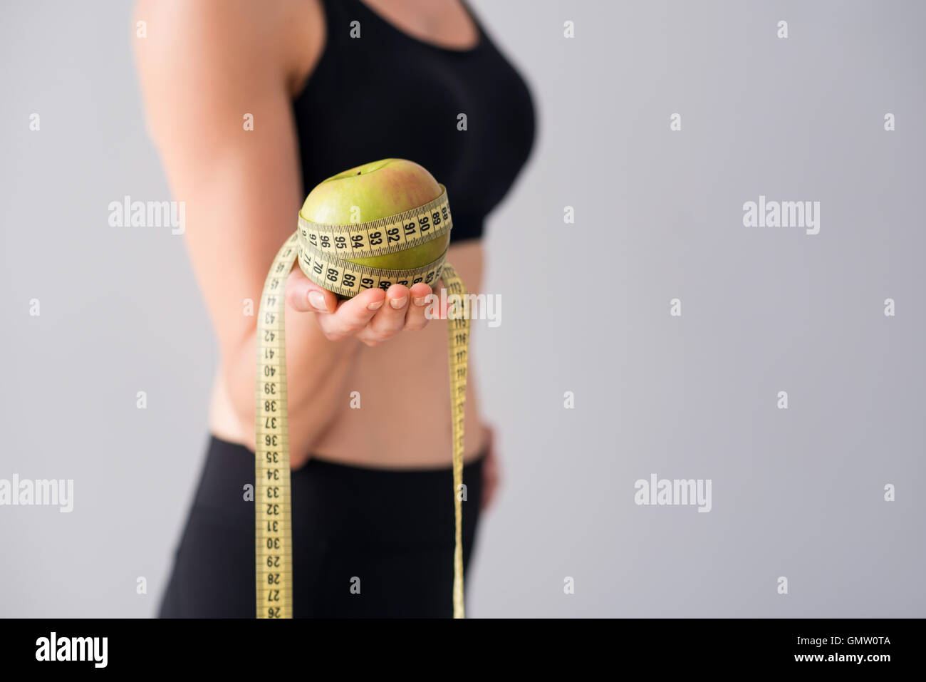 Young woman holding centimeter and apple - Stock Image