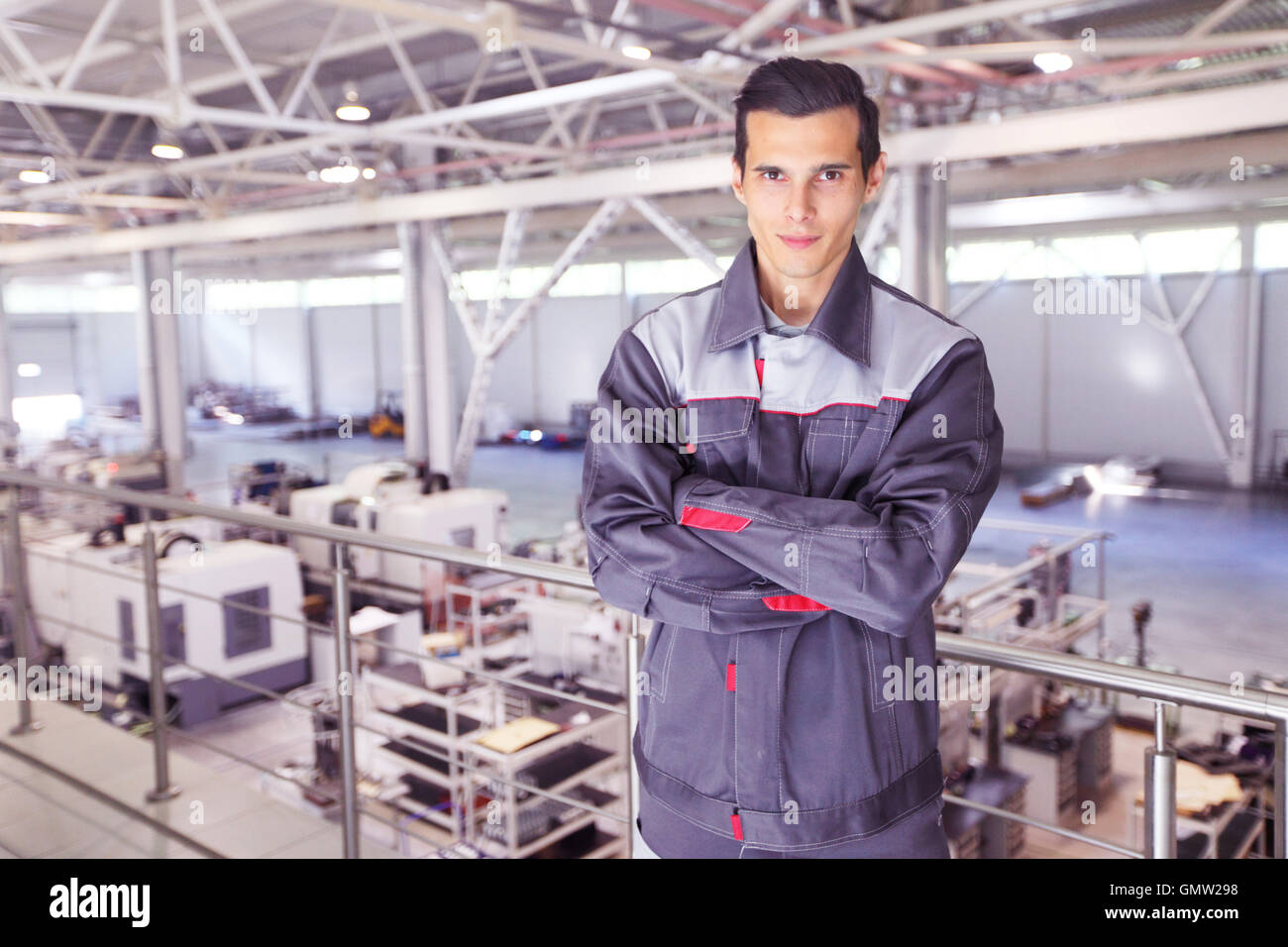 Young worker in uniform standing in CNC factory Stock Photo