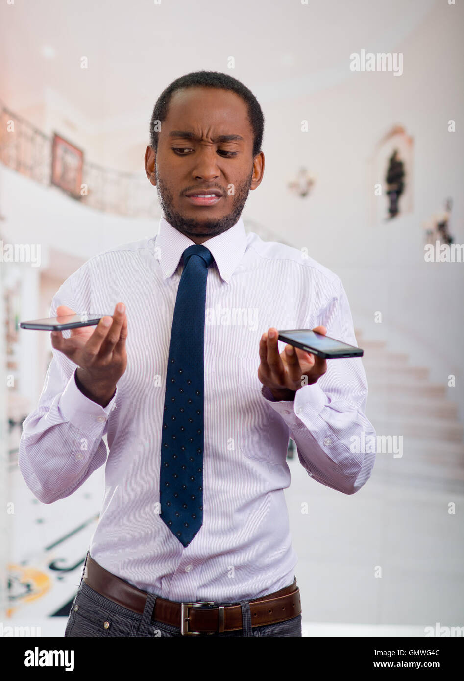 0c47d42cb5ec Handsome man wearing shirt and tie holding up two mobile phones with  stressed facial expression