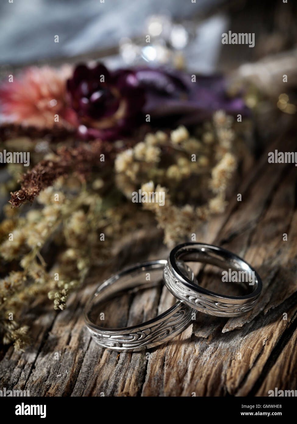 White gold wedding rings with Celtic design and wild dried flowers on rustic background, artistic marriage still - Stock Image